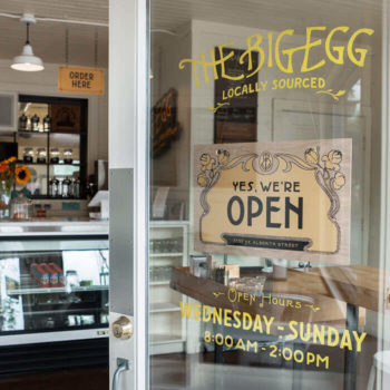 Hand painted sign on front door along with interior of The Big Egg breakfast and brunch cafe